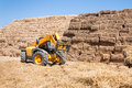 Straw bale stack storage machine and tractor in large farm yard Stock Images