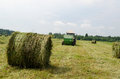 Straw bales agricultural machine gather hay and tractor collect in field near rural village houses Stock Image
