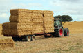 Straw bales, tractor and trailer. Royalty Free Stock Photography