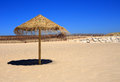 Straw beach sunshade deserted beach near lisbon portugal on a pristine sandy with clear blue sky on the caparica coast Stock Images