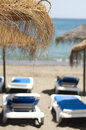 Straw beach umbrellas and sunbeds Royalty Free Stock Photo