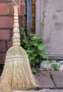 Straw broom closeup of by door with green plants behind Stock Photo