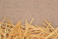 Straw on burlap as background texture Stock Images