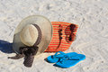 Straw hat, bag, sun glasses and flip flops on a sand beach Royalty Free Stock Photo