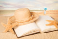 Straw hat on beach book Images libres de droits