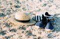 Straw hat and espadrilles lying on the sand on the beach. Summer concept. Holiday relaxing, beach vacation. Royalty Free Stock Photo