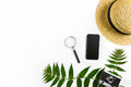 Straw hat with green leaves and old camera on white background, Summer background. Top view Royalty Free Stock Photo