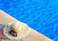 The straw hat and sun glasses lie near to pool Stock Photos