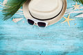 Straw hat, sunglasses, palm leaves, rope, seashell and starfish on blue wooden table top view in flat lay style. Summer holidays. Royalty Free Stock Photo