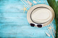 Straw hat, sunglasses, palm leaves, rope, seashell and starfish on table top view, flat lay. Summer holidays, travel, vacation. Royalty Free Stock Photo