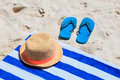 Straw hat, towel and flip flops on a sand beach Royalty Free Stock Photo