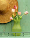 Straw hat and tulips a a vase of herald the impending arrival of summer days to come Royalty Free Stock Photo