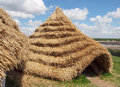 Straw neolithic houses thatched built and reconstructed from chalk and daub and wheat thatched roofing based on Stock Photos
