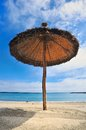 Straw parasol sandy sea beach Royalty Free Stock Photo