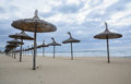 Straw parasols in front row on sandy beach by mediterranean ocean Stock Photo