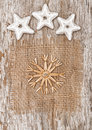 Straw snowflake with stars on textile and old wood the burlap background Royalty Free Stock Photography