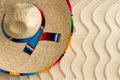 Straw sombrero on golden wavy beach sand view from above of a mexican with a colorful decorative ribbon lying with a ripple effect Stock Image
