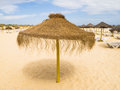 Straw sunshade on a beach in portugal soft sandy algarve there are other with suns beds underneath it is quiet there no Stock Photos