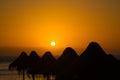 Straw sunshade silhouettes in orange sunset at tenerife island spain Stock Image