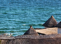 Straw thatched roof against blue sea background Royalty Free Stock Photo
