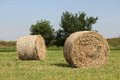 Straw two rolls bale harvesting in the landscape Stock Images