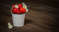 Strawberries and asters in a bucket Royalty Free Stock Photo