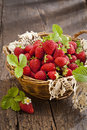 Strawberries in basket on rustic wooden background Royalty Free Stock Photo