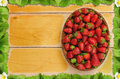 Strawberries in basket on wooden table with a frame of strawberry leaves and flowers - birds eye view Royalty Free Stock Photo