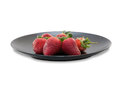 Strawberries on black ceramic plate isolated white background Royalty Free Stock Image