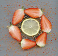 Strawberries black peppercorns chili lemon halved in a circle flakes of pepper and a slice Royalty Free Stock Image