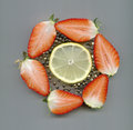 Strawberries black peppercorns and a lemon slice halved in circle Stock Photography