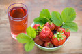 Strawberries in a bowl and a glass of strawberry juice on a wooden table Royalty Free Stock Photo