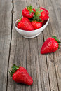 Strawberries in a bowl selective focus white filled with succulent juicy fresh ripe red on an old wooden textured table top Royalty Free Stock Photos