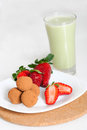 Strawberries and chocolate truffles with matcha latte on a white plate Stock Image
