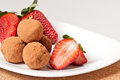 Strawberries and chocolate truffles on a white plate Royalty Free Stock Photos