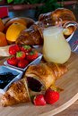 Strawberries croissant breakfast on wooden table Royalty Free Stock Images