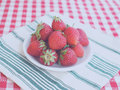 Strawberries and diagonals on a white plate checkered table cloth Royalty Free Stock Photo