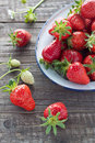 Strawberries in enamel bowl freshly picked an on wooden background Stock Photography