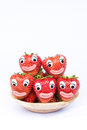 Strawberries with eyes and mouth lying in a wooden bowl Stock Photo