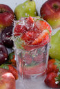 Strawberries falling in glass of water Royalty Free Stock Photos