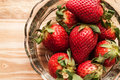 Strawberries in a glass bowl on wooden board Stock Photo