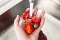 Strawberries in hands under the water. Pure fruit is health Royalty Free Stock Photo