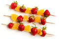 Strawberries and orange on skewers fresh slices the white background Stock Photo
