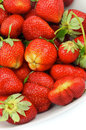 Strawberries perfect ripe with stems straight from garden in white plate closeup Royalty Free Stock Image