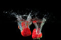 Strawberries splashing into water on a black background Royalty Free Stock Photo