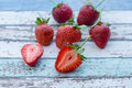 Strawberries on vintage table with one cut in half Royalty Free Stock Photo
