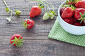 Strawberries in white bowl freshly picked a on wooden background Royalty Free Stock Photography