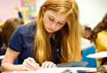 Strawberry blonde teenage girl doing math work Stock Images