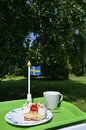 Strawberry cake and a cup on a table with a swedish flag in a garden Stock Photo