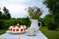 Strawberry cake on a table with summer flowers an a cup outdoors in a garden Royalty Free Stock Image